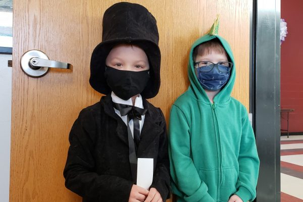 Masked boy dressed as Abraham Lincoln with masked boy in a green dragon costume.