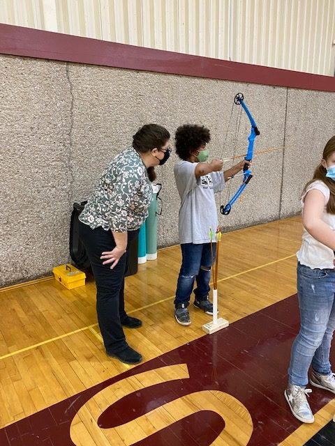 Volunteer Angie Cannon teaches a student to aim a bow and arrow in PE