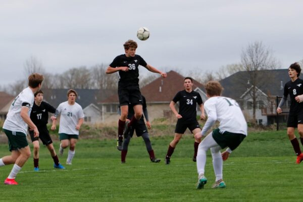 Image of student heading the ball in boys soccer game
