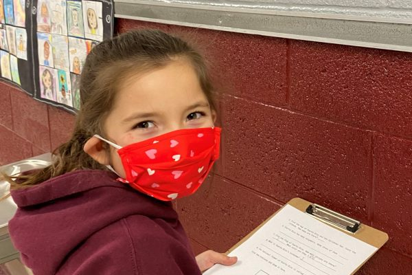 Masked girl holding a clipboard.