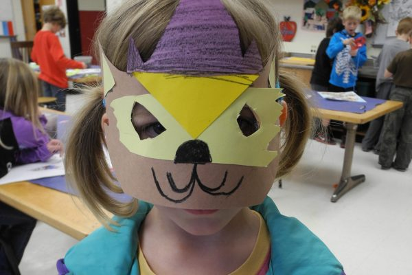Young girl wearing a full decorated mask she made out of construction paper in art class.