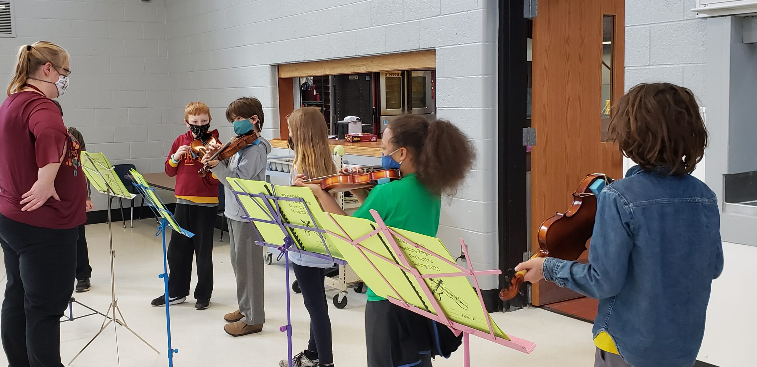Five students practice their string instrument with the orchestra teacher.
