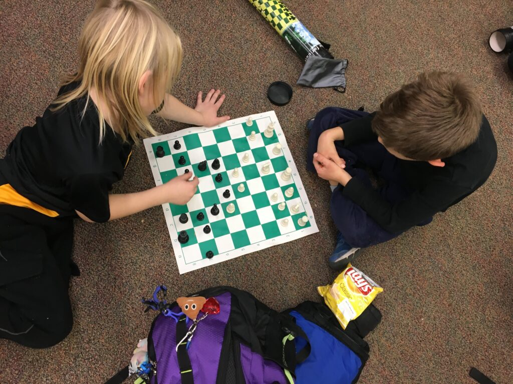 Two students playing chess club.